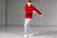 Young male modern dancer dancing. Modern style dancer in red sweater dancing brake dance over grey background. Young talented freestyle dancer royalty free stock photos