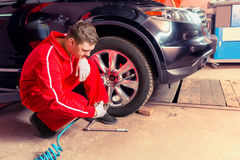 Young male motor mechanic checking the air pressure of a tyre. Crouching down alongside the vehicle with the gauge from the pump in his gloved hand Royalty Free Stock Image