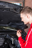 Young male motor mechanic checking the oil level in a car Royalty Free Stock Photography