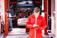 Young male motor mechanic standing making notes in front of a bl. Ack sedan elevated on a hoist in a bay in a garage or workshop Stock Photos