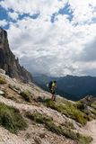 Male climber with an injured knee hiking down a mountain side royalty free stock images