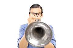 Young male musician blowing into a trumpet Royalty Free Stock Photography