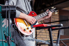Young male musician playing electro guitar during city rock fest Stock Image