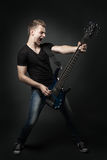 Young male musician playing a six-string bass guitar isolated Stock Image