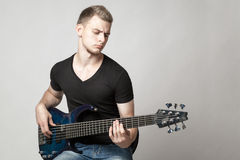 Young male musician playing a six-string bass guitar isolated. On light background Royalty Free Stock Images