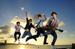 Young male musicians jumping with instruments. Band of young male musicians jumping with instruments against sunset sky background Royalty Free Stock Photos
