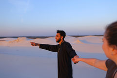 Young male Muslim leads girl by hand and walks along desert at s Royalty Free Stock Images