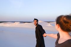 Young male Muslim leads girl by hand and walks along desert at s Stock Photo