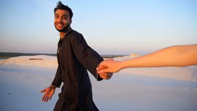 Young male Muslim leads girl by hand and walks along desert at sunset on summer evening.n