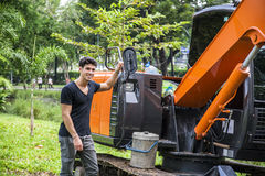 Young male near constructing machine. Young male in casual clothing standing near big constructing machine and smiling on background of green park Royalty Free Stock Photography