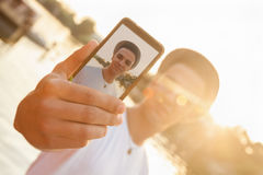 Young Male Near River Taking Selfie. Young Hipster Male Enjoying Near River Taking Selfie Using Smart Phone Stock Photos
