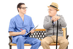 Young male nurse talking to senior gentleman seated on bench Royalty Free Stock Photography