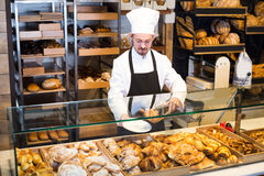 Young male is offering fresh tasty croissant royalty free stock images