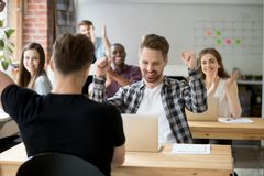 Young male office worker celebrating achievement at work. Young casually dressed male office worker throws hands in air celebrating achievement at work Stock Photography