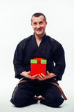 Young male  with orange belt karate fighter training with gift box Royalty Free Stock Photos