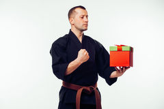 Young male  with orange belt karate fighter training with gift box Royalty Free Stock Photography