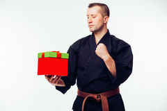 Young male  with orange belt karate fighter training with gift box Stock Photos