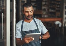 Young male cafe owner using digital tablet royalty free stock photography