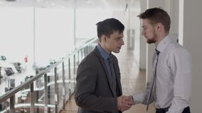 Young male partners is greeting, talking, shaking hands in auto salon. Young male partners is greeting, talking, shaking hands in auto salon, two businessmen stock video