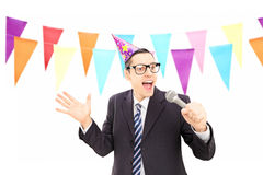 Young male with party hat singing during a celebration Royalty Free Stock Photography