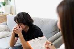 Young male patient crying on sofa consulting with female psychologist. stock image