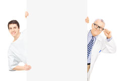 Young male patient and middle aged doctor standing behind panel Stock Images