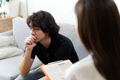 Young stress male patient sitting on sofa consulting with female psychologist. stock photography