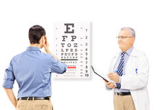 Young male patient taking eyesight test and an optician holding Royalty Free Stock Photography