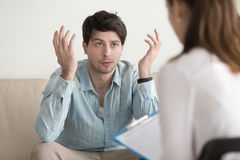 Young male patient talking about his problem to female psychothe stock photography