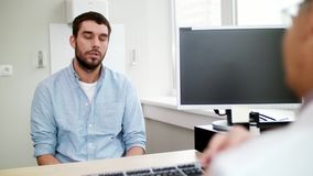Young male patient talking to doctor at hospital. Medicine, healthcare and people concept - young male patient having health problem talking to doctor at stock footage