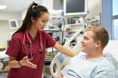 Young Male Patient Talking To Female Nurse In Emergency Room Royalty Free Stock Photo