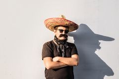 Young male person dressed up in traditional mexican sombrero, fa. Lse moustache, bandana and sunglasses. Festival or halloween concept of man posing as bandit or stock photos