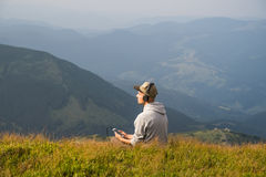 Man sits top of the hill in carpathian mountains and listens to music in headphones and enjoys beautiful view Stock Images