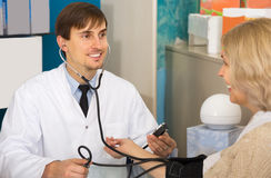 Young male pharmaceutist taking  mature patients blood pressure. Using  sphygmomanometer in pharmacy drugstore Stock Images