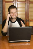 Young male on phone smiling. Pointing at computer Royalty Free Stock Photography
