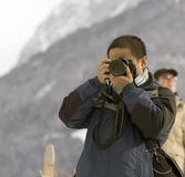 Young male photographer. With camera taking photos Stock Image