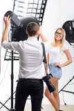 Young male photographer adjusting spotlight for. Spotlight regulation. Young male professional photographer adjusts spotlight while model poses stock image