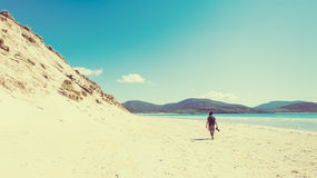 Young male photographer with dreadlocks at a sunny white sand beach. With high sand dunes, Luskentyre, Isle of Harris, Hebrides, Scotland stock photography