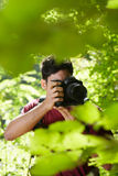 Young male photographer hiking in forest Royalty Free Stock Photo