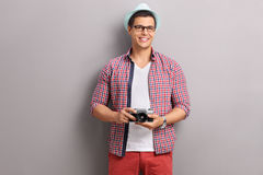 Young male photographer holding a camera. And posing in front of a gray wall Royalty Free Stock Photos