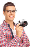 Young male photographer holding a camera. Vertical shot of a young male photographer holding a camera and posing isolated on white background Royalty Free Stock Image
