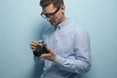 Young male photographer holding a new camera stock photography