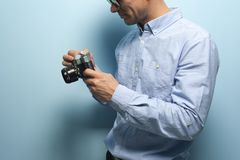 Young male photographer holding vintage camera stock photography