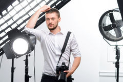 Young male photographer leans on the spotlight Royalty Free Stock Photography
