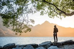 Young male photographer looking at sunset in Queenstown. Young male photographer looking at scenery of Lake Wakatipu during golden hour sunset in Queenstown Royalty Free Stock Photos