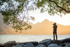 Young male photographer looking at sunset in Queenstown. Young male photographer looking at scenery of Lake Wakatipu during golden hour sunset in Queenstown Royalty Free Stock Photo
