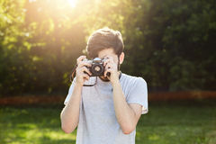 Young male photographer making photos with vintage camera while standing at green grass. Professional male using retro camera phot Stock Photography