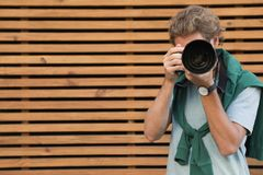 Young male photographer with professional camera near wooden wall royalty free stock photos