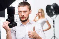 Young male photographer showing thumbs up. Good work. Nice-looking young male photographer holds up a camera while showing thumbs up stock photography