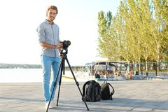 Young male photographer standing with professional camera stock image